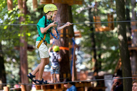 Profile of young cute child boy in safety harness and helmet attached with carbine to cable moves slowly along rope way on sunny bokeh background. Sport, game, leisure, outdoor activity concept.