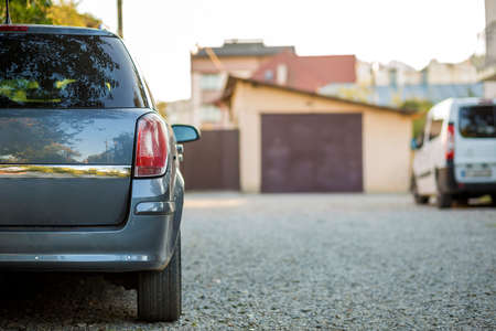 New shiny gray car parked on gravel suburbs road on blurred sunny summer background. Banco de Imagens