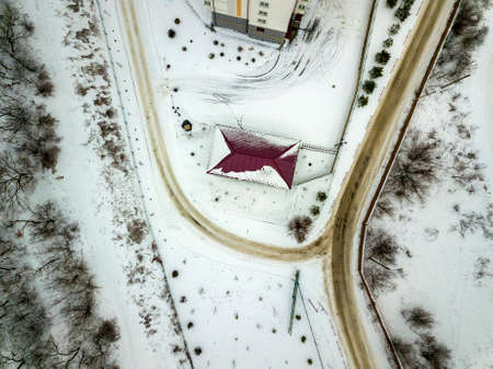 Aerial winter top view of house roof on fenced property, snowy field and dirty road.