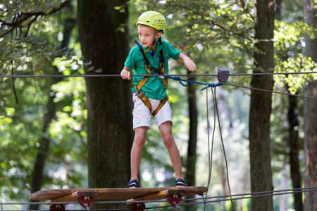 Young cute child boy in summer clothing, safety harness and helmet attached with carbine to cable moves slowly along rope way on green trees sunny bokeh background. Sport, game, leisure concept. Reklamní fotografie