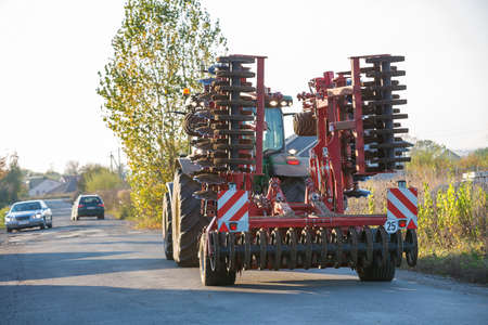 Tractor combine with disc harrows driving along rural road on sunny day. Agricultural machinery and farming concept.