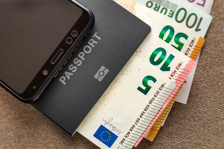 Modern black cellphone, Euro money banknotes bills and travel passport on copy space background. Travelling light, comfortable journey concept.