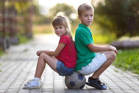Two cute blond happy young children, smiling boy and long-haired girl sitting back-to-back on soccer ball on empty sunny suburb paved road blurred summer bright background. Children games concept. Stok Fotoğraf