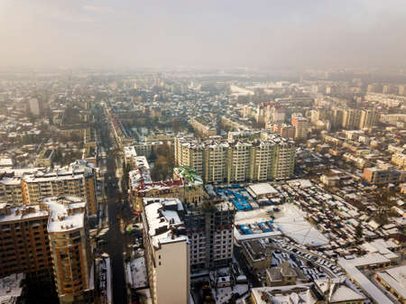 Aerial black and white winter top view of modern city center with tall buildings and parked cars on snowy streets.