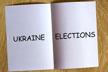 White sheen of paper on wooden background with text Ukraine elections on it.