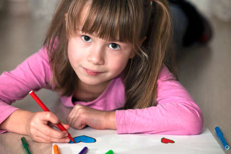Child girl drawing with colorful pencils crayons heart on white paper. Art education, creativity concept. Stock Photo