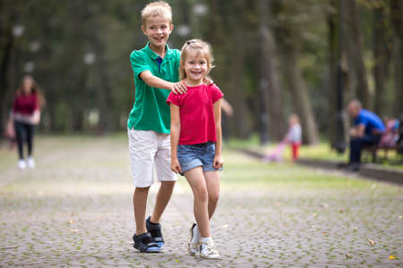 Two cute young laughing children, girl and boy, brother and sister having fun on blurred bright sunny summer park alley green trees bokeh background. Games and recreation, happy childhood concept. Stock Photo