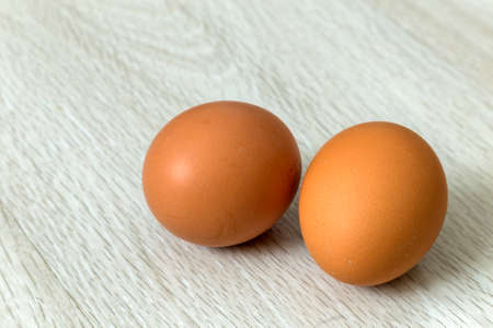 Hen eggs on kitchen table background. Healthy organic food, delicious meal, cholesterol and diet concept.