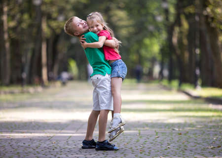 Two cute young funny smiling children, girl and boy, brother holding sister in his arms, having fun on blurred bright sunny park alley green trees bokeh background. Loving siblings relations concept.