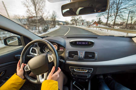 Modern car interior with driver female hands on steering wheel, winter snowy landscape outside. Safe driving concept.