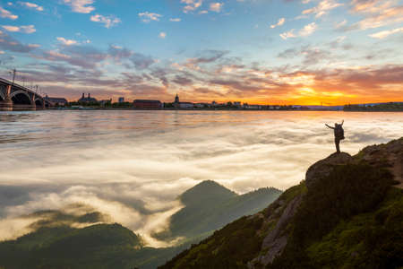 Small silhouette of tourist with backpack on rocky mountain slope with raised hands at sunrise on background of valley or river covered with white puffy clouds, bridge and city landscape. Stock Photo
