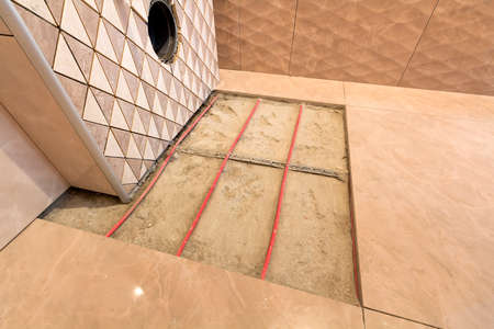 Unfinished reconstruction of bathroom with ceramic tiles installed on walls, heating electrical cables system on cement floor and place for toilet. Imagens