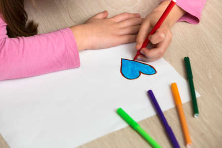 Child girl hands drawing with colorful pencils crayons heart on white paper. Art education, creativity concept.