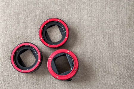 Close-up of macro rings, camera adapters on light cloth copy space background. Modern technology and photography equipment concept. Stock Photo