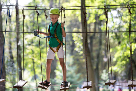 Young smiling cute child boy in safety harness and helmet attached with carbine to cable moves confidently along rope way on green foliage sunny bokeh background. Sport, game, leisure concept.