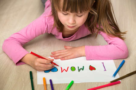 Cute child girl drawing with colorful crayons I love Mom on white paper. Art education, creativity concept.