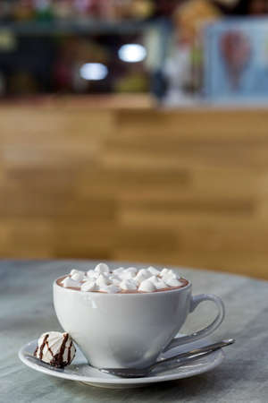 Composition of mug of coffee with marshmallows on porcelain plate on light background, top view. Stock Photo