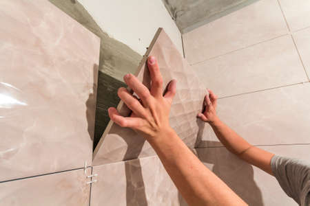 Close-up of worker tiler hands installing light beige ceramic tiles on walls of future bathroom. Tiles installation, home improvement, renovation and construction, comfortable modern home concept.