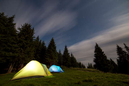 Two brightly lit tourist tents on green grassy forest clearing among tall pine trees on clear dark blue starry sky background. Tourism, night camping in summer mountains, beauty of nature concept. Stock Photo
