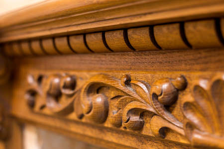 Close-up detail of carved wooden decorative piece of furniture with floral ornament made of natural hardwood. Art craft and design concept. Standard-Bild - 119777177