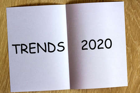 White sheen of paper on wooden background with text Trends 2020 on it.