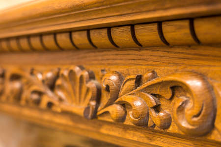 Close-up detail of carved wooden decorative piece of furniture with floral ornament made of natural hardwood. Art craft and design concept. Banco de Imagens