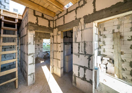 House room interior under construction and renovation. Energy saving walls of hollow foam insulation blocks, wooden ceiling beams and roof frame. Stok Fotoğraf