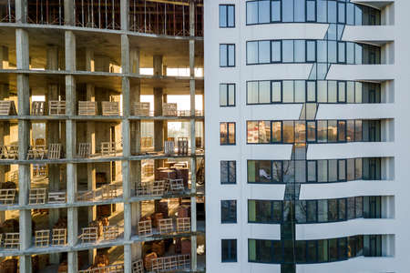 Close-up comparison of tall multi storied modern apartment or office building with shiny windows and unfinished building under construction. Imagens