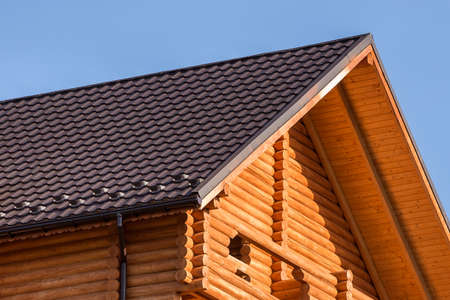 Close-up detail of new modern wooden warm ecological cottage house top with shingled brown roof and wooden sidings on blue sky background. Professionally done carpentry and construction work.
