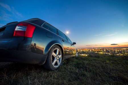 Black car parked at night in green meadows on copy space background of lights of distant city buildings and bright blue sky with first star at sunset. Imagens