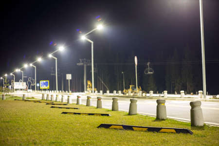 Empty parking lot on green lawn brightly illuminated by street lamps along road on dark night sky copy space background.