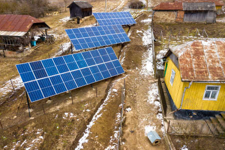 Aerial top view of stand-alone blue shiny solar photo voltaic panel systems producing renewable clean energy in rural residential area on sunny winter day.