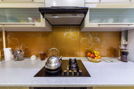 Shiny stainless tea kettle teapot with boiling water on burning gas stove on modern kitchen yellow interior background.