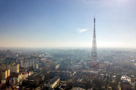 Aerial view of modern city urban foggy landscape with tall television tower on bright blue sky copy space background at dawn. Drone photography. Imagens