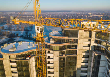 Apartment or office tall building under construction, top view. Tower crane on bright blue sky copy space background, city landscape stretching to horizon. Drone aerial photography.