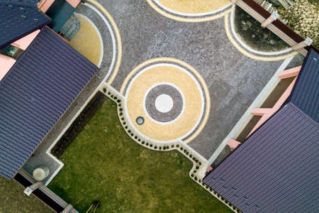 Aerial top view of house shingle roof on background of green lawn and colorful paved yard with geometrical abstract pattern. Imagens