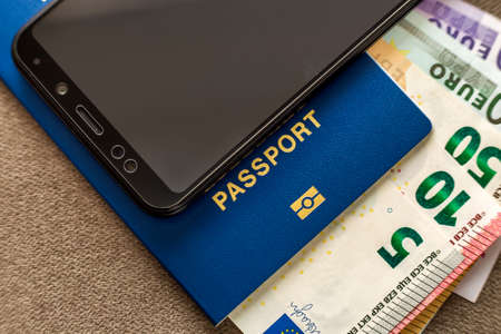 Modern black cellphone, Euro money banknotes bills and travel passport. Travelling light, comfortable journey concept.