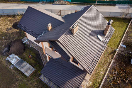 Aerial top view of building steep shingle roof, brick chimneys and small attic window on house top with metal tile roof. Roofing, repair and renovation work.
