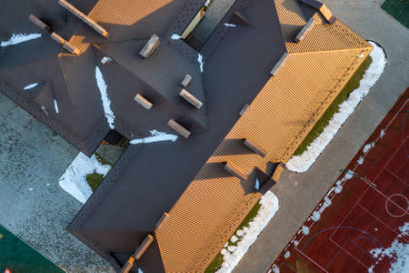Top aerial view of building brown shingle tiled roof with complex configuration construction. Abstract background, geometrical pattern.