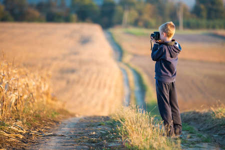 Young child boy with photo camera taking picture of wheat field on blurred rural background.