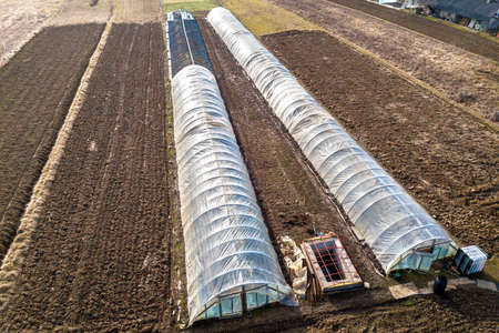 Aerial view of long arched greenhouses covered with polyethylene in plowed spring field. Agriculture and farming.