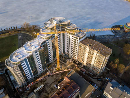 Apartment or office tall building under construction, top view. Tower crane and city landscape stretching to horizon. Drone aerial photography.