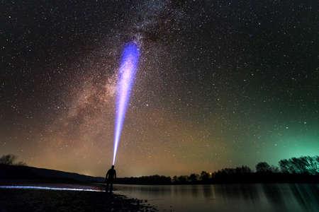Vista posteriore dell'uomo con la torcia frontale in piedi sulla riva del fiume, lungo raggio blu attraverso il bellissimo cielo stellato scuro. Concetto di fotografia notturna. Ampio panorama, copia dello sfondo dello spazio.