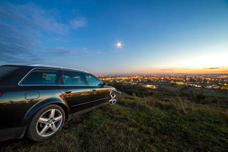 Black car parked at night in green meadows on copy space background of lights of distant city buildings and bright blue sky with first star at sunset. 免版税图像