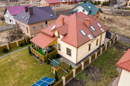 Aerial top view of residential area with new houses with roof solar photo voltaic panels, wind turbine mill and stand-alone exterior solar panel systems. Renewable green energy generation concept. Banque d'images