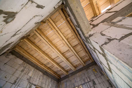 Close-up detail of house room interior under construction and renovation. Energy saving walls of hollow foam insulation blocks, wooden ceiling beams for roof frame.
