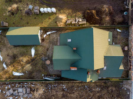Aerial view of new residential house cottage and garage or barn with shingle roof on fenced yard on sunny day. Banque d'images - 121481350