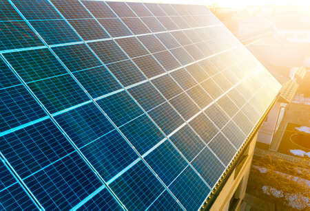 Close-up oppervlak van verlicht door de zon blauwe glanzende fotovoltaïsche panelen. Systeem dat hernieuwbare schone energie produceert. Hernieuwbaar ecologisch groen energieproductieconcept.