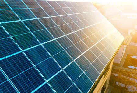 Superficie de primer plano iluminado por paneles fotovoltaicos solares brillantes de color azul sol. Sistema de producción de energía limpia renovable. Concepto de producción de energía verde ecológica renovable.