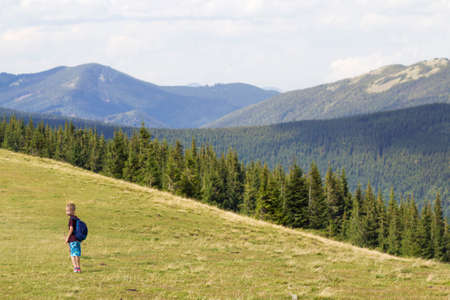 Young happy child boy with backpack walking in mountain grassy valley on background of summer woody mountain. Active lifestyle, adventure and weekend activity concept.